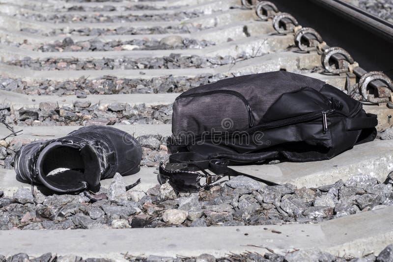 Linii kolejowej skrzyżowanie na nim jest plecak, buty, szkła Pojęcie narosła uwaga sposoby fotografia royalty free