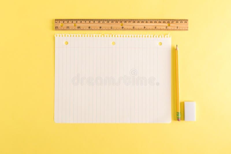 Linjalen och ett tomt ark av anteckningsboken skyler över brister arkivfoto