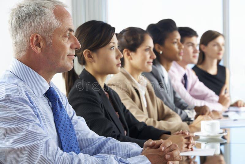 Linje av affärsfolk som lyssnar till presentationen som placeras på Glas arkivfoton
