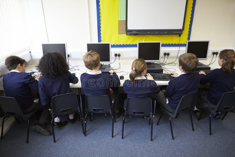 Linje av barn i skoladatorgrupp arkivfoton
