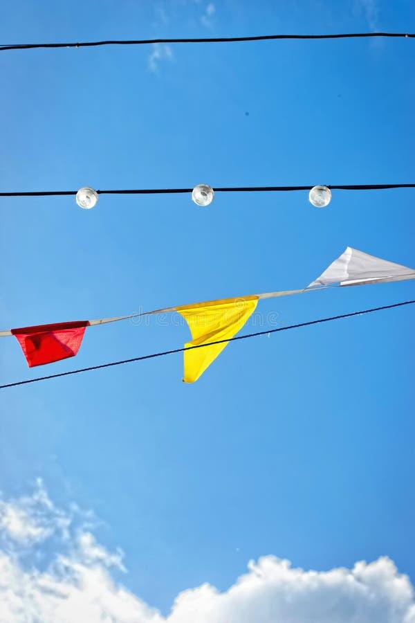 Linje av färgglade festivalflaggor och lampor mot blå himmel arkivfoto