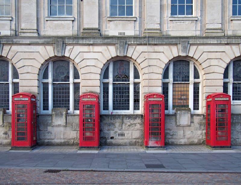 Linje av fyra traditionella brittiska röda telefonaskar utanför en gammal stolpe - kontorsbyggnad i blackpool England arkivbilder