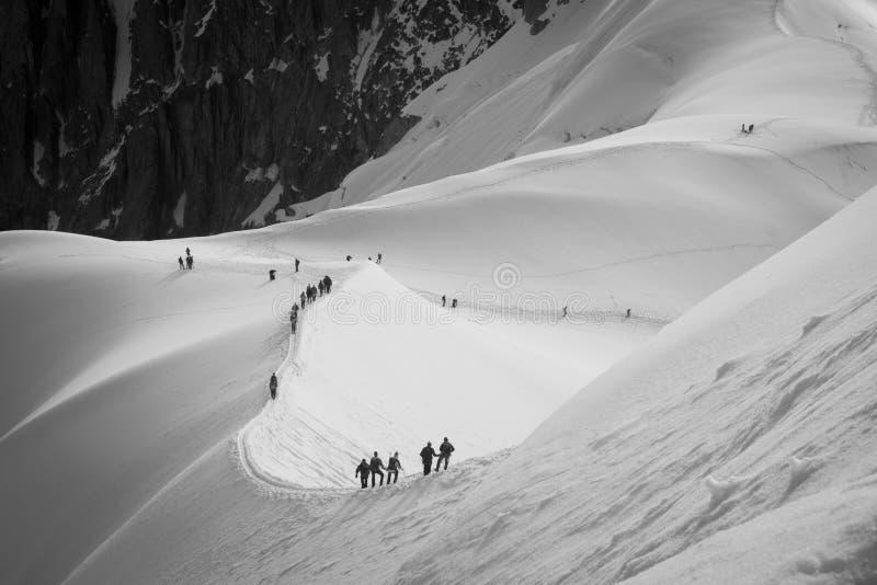 Linje av roped-upp lag av bergsbestigare på kanten som stiger ned från station för Aiguille du Midi kabelbil royaltyfri foto