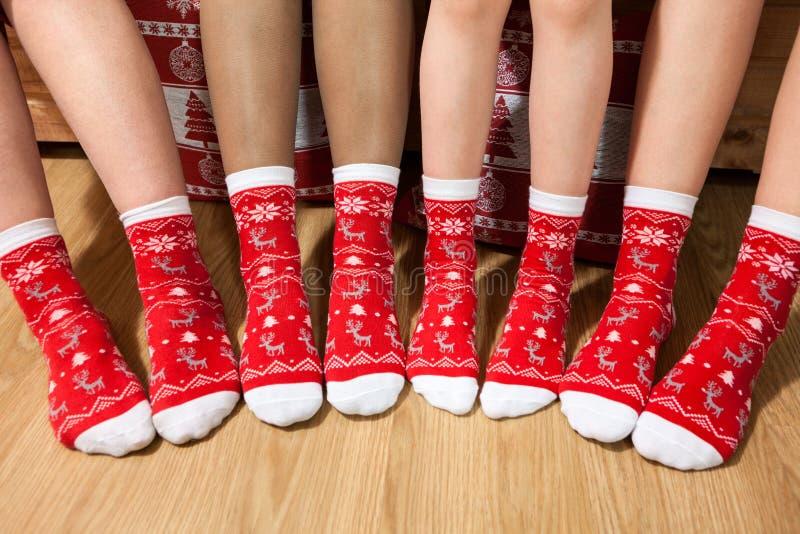 Linje från mänsklig fot som tillsammans bär röda julsockor, vuxna människor och barnben arkivbild