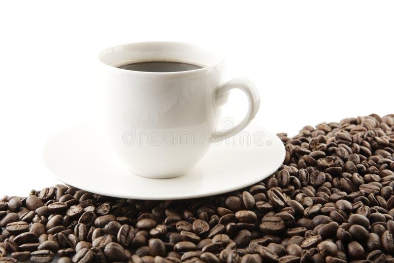 Linje som göras av kaffebönor med koppen kaffe royaltyfri fotografi