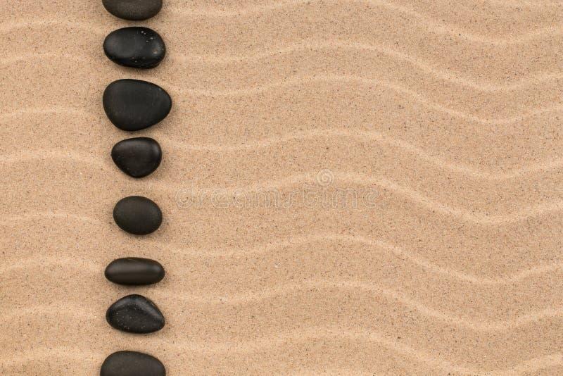 Linje som göras av svartstenar bland sanddyn royaltyfri fotografi