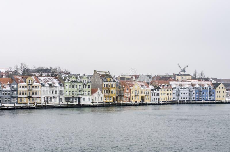 Linjen av färgrika hus bredvid vattnet med en vind maler i en bakgrund arkivfoto