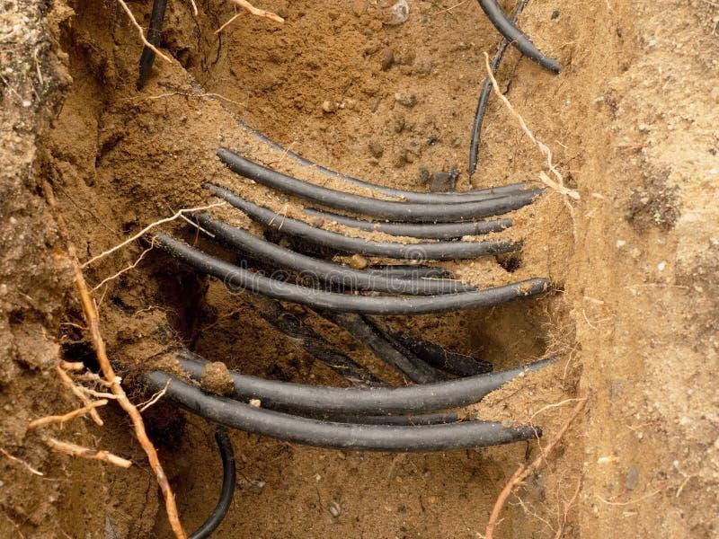 Linjer av metallisk och optiska kablar för fiber, konstruktion av optisk nätverksanslutning för kommunikation royaltyfria bilder