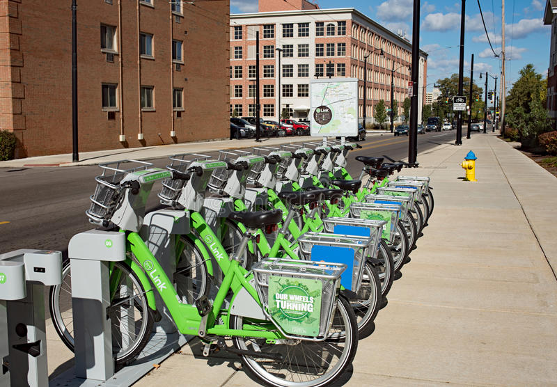 Link Dayton Bike Share. Dayton, Ohio, USA - October 18, 2015: Green Link bicycles stand in morning light near University of Dayton waiting to be rented as part royalty free stock image