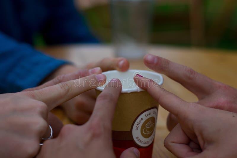 Linkebeek, B?lgica - 8 de junho de 2018: Grupo de amigos que tocam no dedo no copo de caf? imagens de stock royalty free