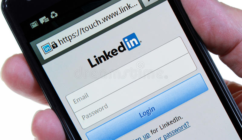 Linkedin Login Page. Palm Springs, California, USA - May 24, 2013: A hand holding a smartphone displaying the Linkedin login page. Linkedin is a professional