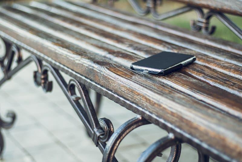 Linkersmartphone op een houten bank in stedelijk openbaar park Verloren en vergeten persoonlijk ding in openlucht in de stad stock fotografie