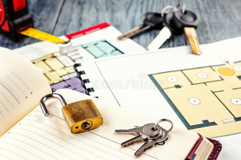 Linking new key on project plan of apartment house. Concept new residence house warming Buying Selling Real Estate royalty free stock photography