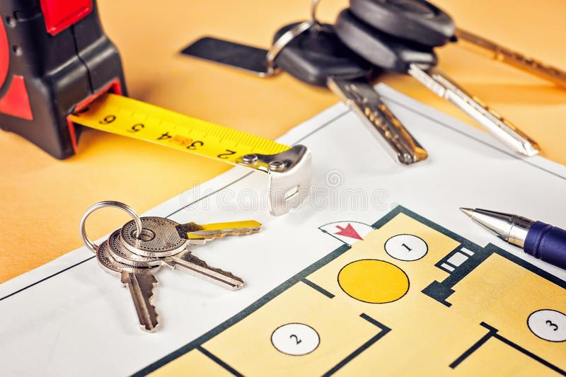 Linking new key on project plan of apartment house. Concept new residence house warming Buying Selling Real Estate stock image