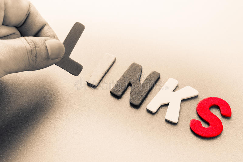 Links. Finger pick a wood letters of Links word stock photography