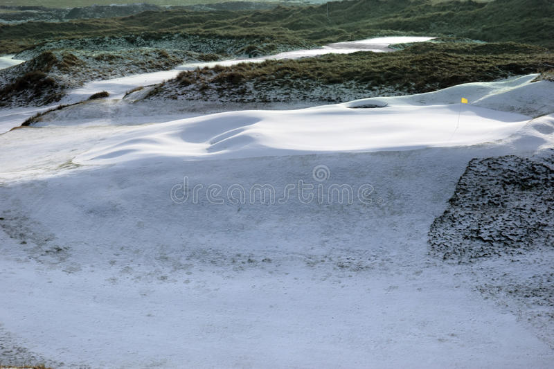Links golf course green with snow and yellow flag. A snow covered links golf hole in ireland in winter weather with yellow flag stock image