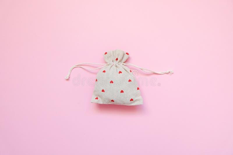 Linnenzak met rode harten op roze achtergrond De dag van de valentijnskaart `s r Vlak leg, hoogste mening stock foto's