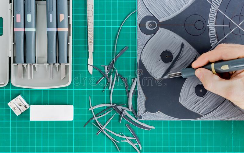 Lino cutting in art class close up. Lino cutting tools on a desktop. Lino cutting in arrt class royalty free stock image