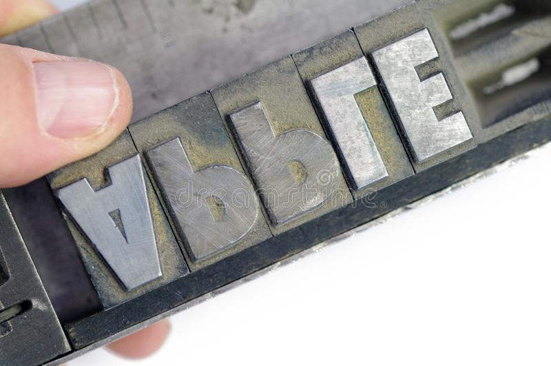 Linotypetekst in stok met dichte de appel van de handspelling royalty-vrije stock afbeelding