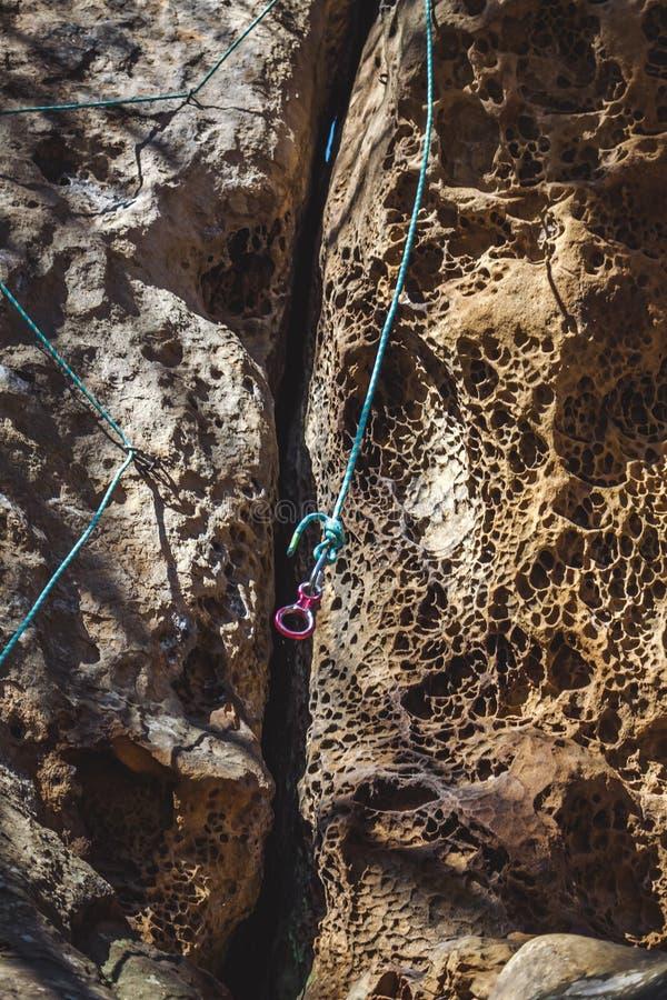 Linowy witn postaci 8 belay przyrząd na piaskowcowej falezie w lesie zdjęcia stock