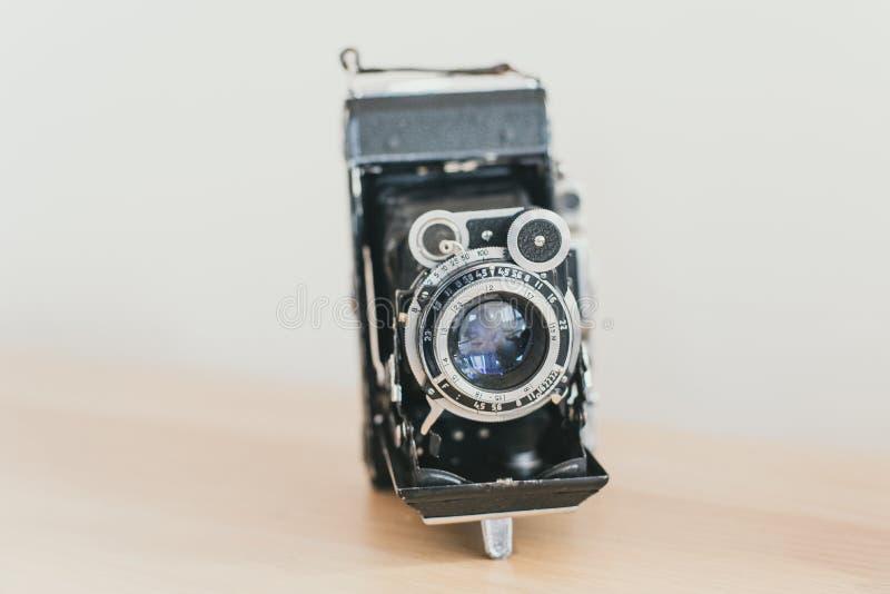 linsdragspel på en gammal kamera Gammal tappningkamera på en träljus bakgrund royaltyfri bild