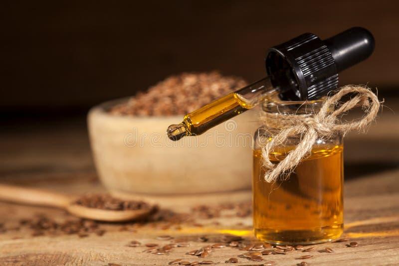 Linseed olej, łyżka i puchar linseeds na drewnianym tle, fotografia stock