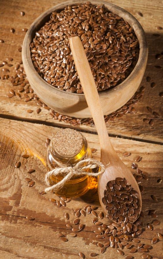 Linseed olej i puchar linseeds na drewnianym tle obrazy royalty free