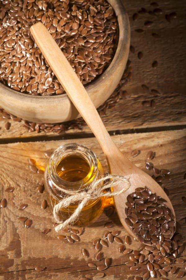 Linseed olej i puchar linseeds na drewnianym tle zdjęcia royalty free