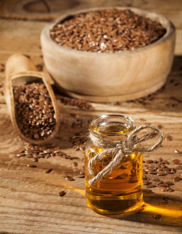 Linseed olej i puchar linseeds na drewnianym tle fotografia stock