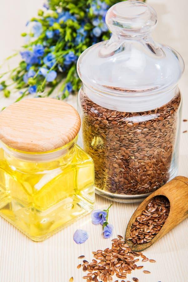 Linseed olej, lnów ziarna i kwiaty na lekkim tle, obrazy stock
