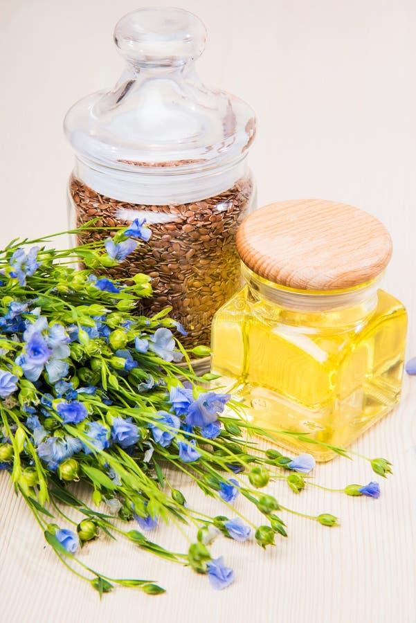 Linseed olej, lnów ziarna i kwiaty na lekkim tle, fotografia royalty free