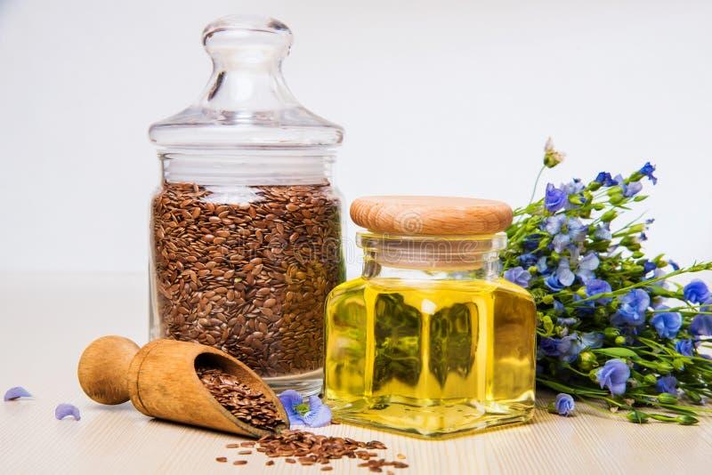 Linseed olej, lnów ziarna i kwiaty na lekkim tle, zdjęcie royalty free