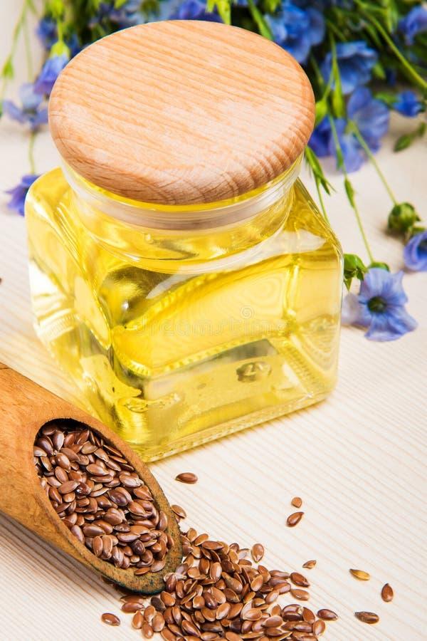 Linseed olej, lnów ziarna i kwiaty na lekkim tle, fotografia stock