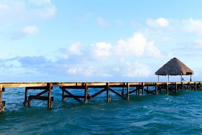 Lint houten gazebo en stoel op het strand bij zonsondergang of zonsopgang Achtergrond van een kust met zetel, rustend paviljoen,  royalty-vrije stock foto