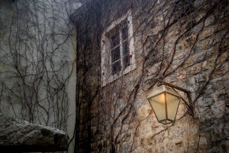 Linterna ardiendo en la pared de la ciudad vieja foto de archivo
