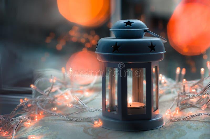 Linterna azul marino y gris de la vela con las luces de la Navidad y el bokeh anaranjados borrosos fotografía de archivo libre de regalías
