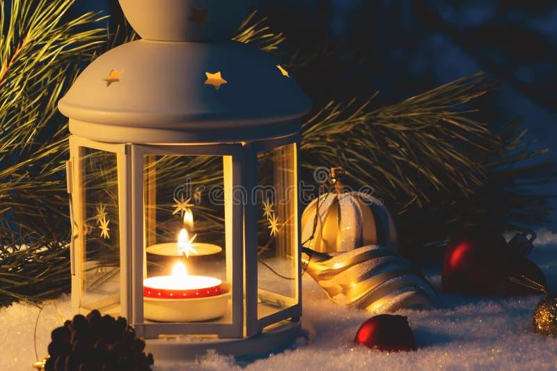 Linterna con una vela ardiente y decoraciones de la Navidad en una tabla nevada fotografía de archivo libre de regalías