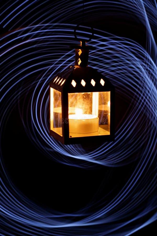 linterna con una vela en la oscuridad contra un fondo de las líneas dibujadas por un freezelight imagen de archivo