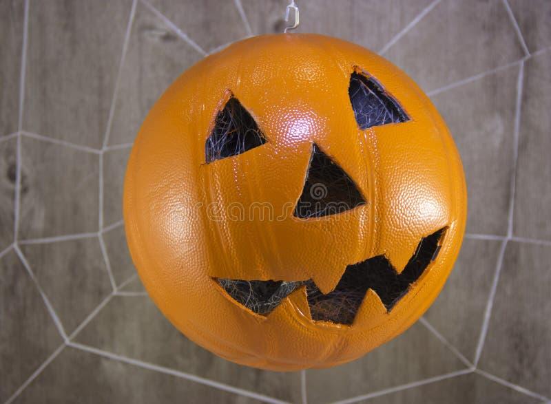 Linterna de Jack para Halloween de un baloncesto en un fondo de madera con las web de araña foto de archivo