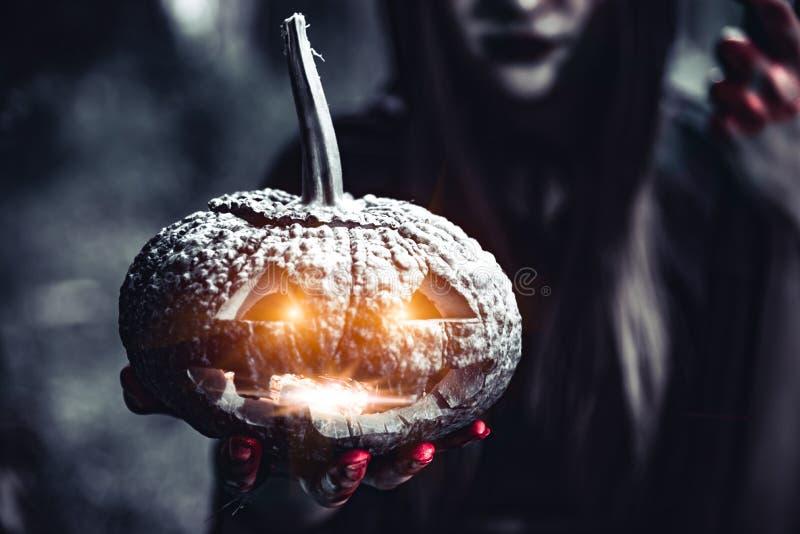 Linterna de la calabaza en mano de la bruja Calabaza de la tenencia de la mujer mayor en el d?a de Halloween del bosque y el conc foto de archivo libre de regalías