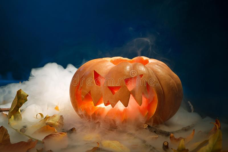 Linterna de la calabaza de Halloween con las hojas secas con las velas ardientes imágenes de archivo libres de regalías