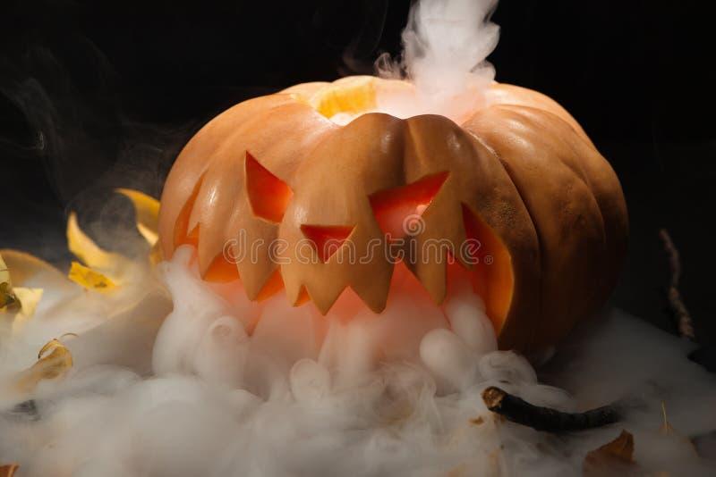 Linterna de la calabaza de Halloween con las hojas secas con las velas ardientes imagen de archivo
