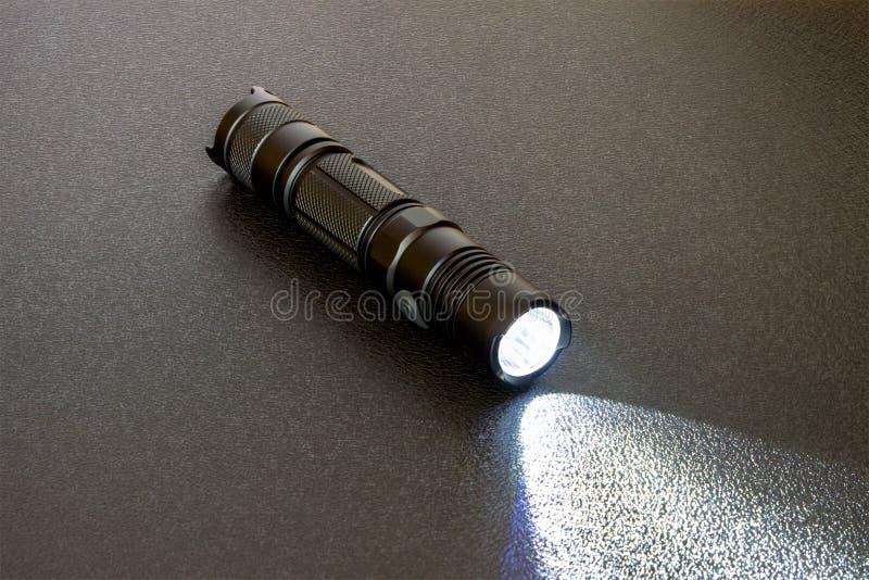 Linterna de LED negra metálica en un fondo negro Haz luminoso en fondo de textura fotografía de archivo libre de regalías