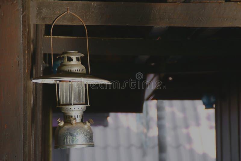 Linterna de tormenta vieja del huracán, ejecución de la lámpara de keroseno en haz de madera imagen de archivo