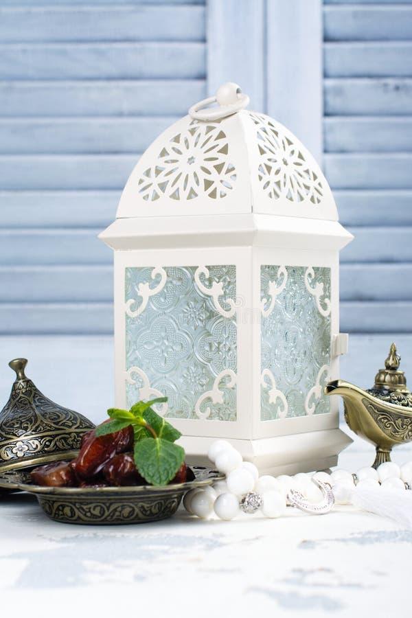 Linterna, fechas, lámpara de aladdin y rosario árabes en el fondo blanco imagenes de archivo