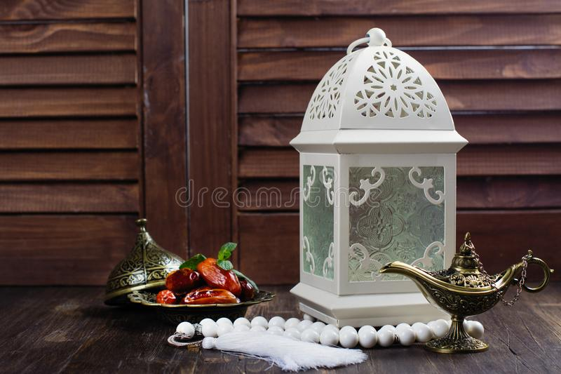 Linterna, fechas, lámpara de aladdin y rosario árabes en fondo de madera imagen de archivo