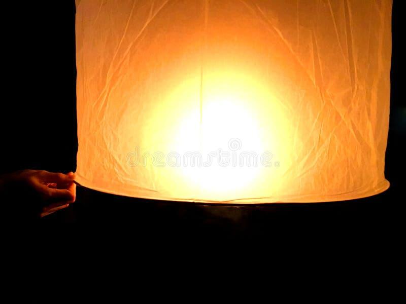 Linterna flotante de papel que se sostiene a mano durante el fuego que espera quemado en la cera para hacerlo humo para el empuje fotos de archivo