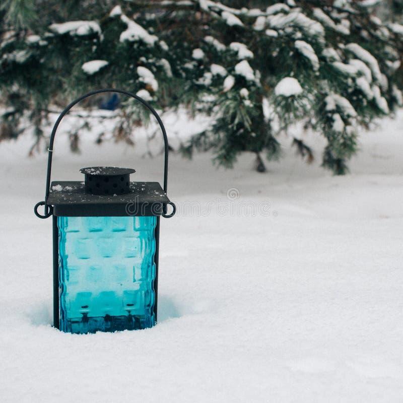 linterna negra y azul en la nieve contra ramas nevadas Fondo hermoso del invierno, espacio de la copia fotos de archivo libres de regalías