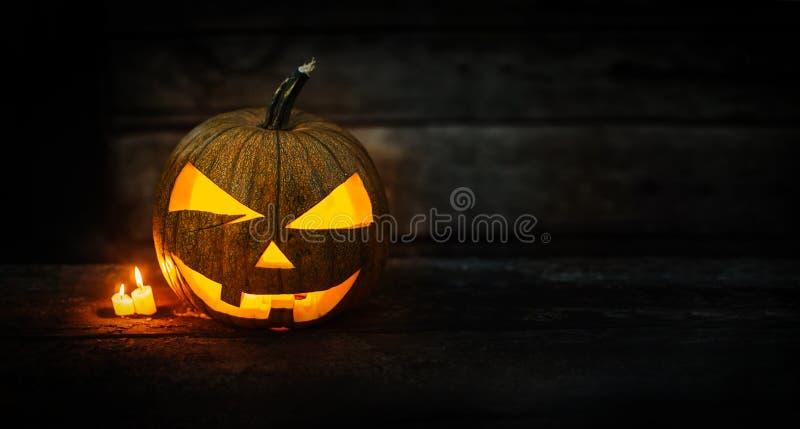 Linterna principal del enchufe de la calabaza de Halloween con las velas ardientes en fondo cambiante oscuro imagen de archivo libre de regalías