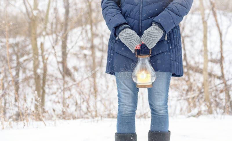 Linterna que se sostiene exterior derecha de la mujer mientras que está cayendo la nieve fotos de archivo